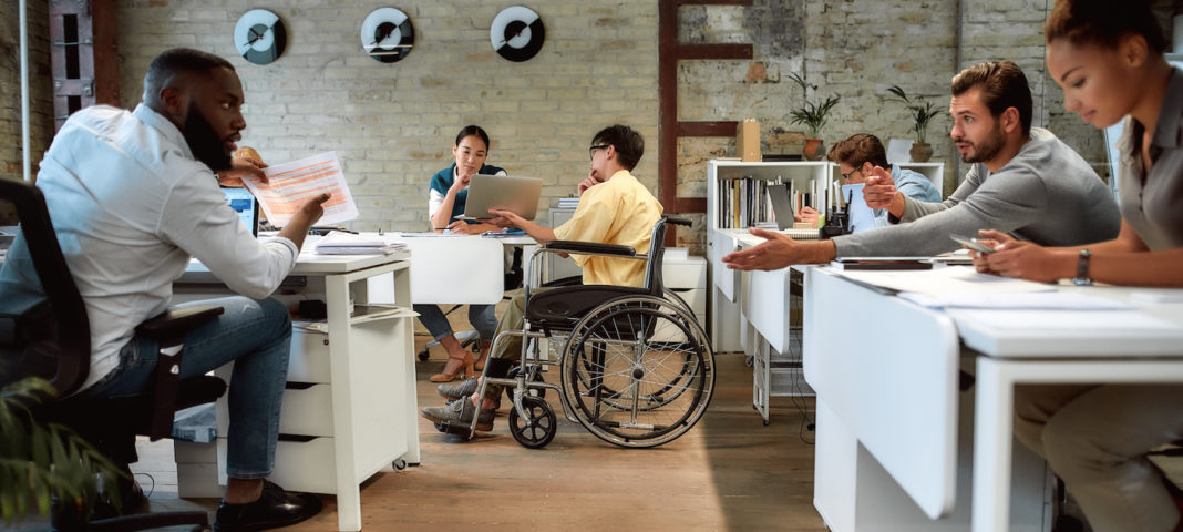 Portrait of young male worker in wheelchair talking to female colleague while presenting ideas using laptop in co-working space.